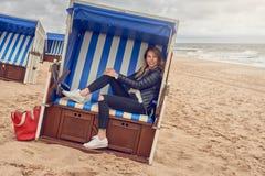 坐在海滩小屋的可爱的苗条白肤金发的妇女 免版税库存照片