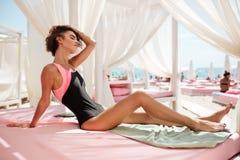 坐在海滩帐篷和梦想闭合值的眼睛的时髦泳装的美丽的女孩,当整理她的头发时 画象  免版税库存照片