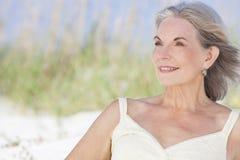 坐在海滩的可爱的高级妇女 免版税库存照片