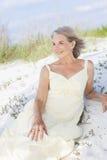 坐在海滩的可爱的高级妇女 库存图片