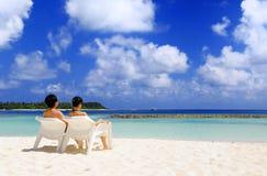 坐在海滩的夫妇 库存照片