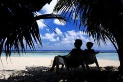 坐在海滩的夫妇 免版税库存照片