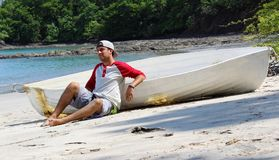 坐在海滩的悦目遭难的人由与海洋和密林的被击毁的小船等待的帮助在背景中 免版税库存图片