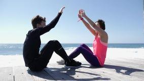 坐在海滩附近的愉快的年轻人和妇女高fives 飞溅agains的波浪岩石 年轻夫妇上流五 t 股票录像