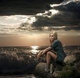 坐在海运附近的美丽的白肤金发的妇女 免版税库存照片
