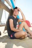 坐在海滩的可爱的年轻人 免版税库存图片