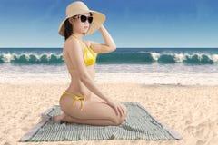 坐在海滨的妇女佩带的游泳衣 免版税图库摄影
