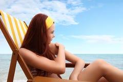 坐在海滩的妇女您投入了遮光剂 库存图片