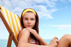 坐在海滩的妇女您投入了遮光剂 免版税图库摄影