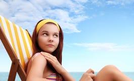 坐在海滩的妇女您投入了遮光剂 库存照片