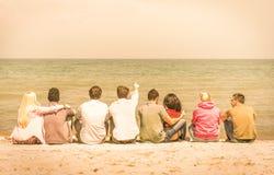 坐在海滩的小组国际多种族朋友 库存照片