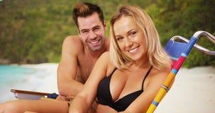 坐在海滩的愉快的悦目千福年的夫妇微笑对照相机 免版税图库摄影