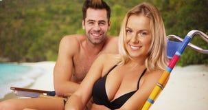 坐在海滩的愉快的悦目千福年的夫妇微笑对照相机 免版税库存图片