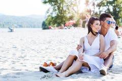 坐在海滩的浪漫年轻夫妇 免版税库存图片