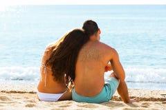 坐在海滩的背面图夫妇 免版税库存图片