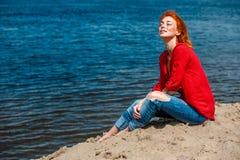 坐在海滩的年轻美丽的红头发人妇女 库存照片