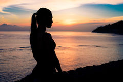 坐在海洋附近的妇女的剪影 免版税库存照片