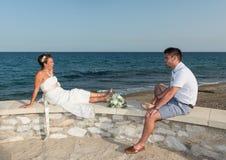 坐在海滩附近的新娘和新郎 库存照片