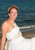 坐在海滩附近的新娘 免版税库存图片