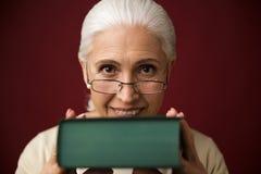坐在深蓝背景的老妇人拿着书 免版税库存图片
