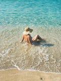 坐在清楚的海水的比基尼泳装的资深妇女游人 免版税库存照片