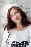 坐在温暖的白色盖帽的窗口附近的美丽的微笑的女孩 库存图片