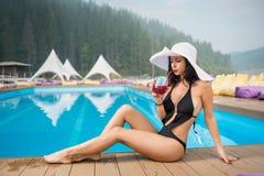 坐在游泳池和饮用的鸡尾酒旁边的帽子和黑比基尼泳装的年轻美丽的夫人 免版税库存图片
