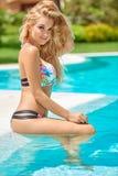 坐在游泳池的可爱的白肤金发的女孩 免版税库存照片