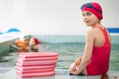 坐在游泳池的孩子 库存照片