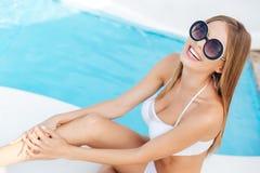 坐在游泳池的微笑的白肤金发的女孩 库存图片