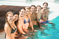 坐在游泳池的朋友画象  免版税库存图片