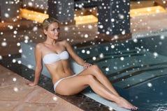 坐在游泳池的比基尼泳装的愉快的妇女 免版税库存照片