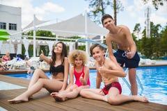坐在游泳池的边缘的少年朋友 库存照片