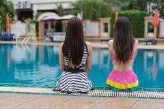 坐在游泳池边缘的两个妇女朋友 免版税库存照片