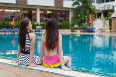 坐在游泳池边缘的两个妇女朋友 免版税图库摄影