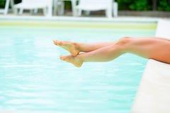 坐在游泳池附近的妇女Д egs 免版税图库摄影