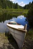 坐在湖旁边的小船 免版税库存图片
