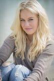 坐在湖的白肤金发的妇女 免版税库存图片