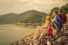 坐在湖附近的愉快的家庭在天时间 库存图片