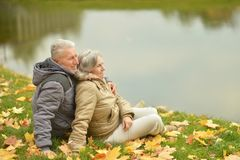 坐在湖附近的成熟夫妇 免版税库存图片
