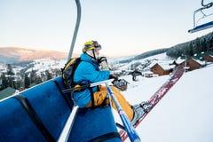 坐在滑雪升降椅的滑雪者人在美好的天 免版税库存照片