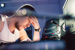 坐在演播室特写镜头的疲乏的dj 免版税库存照片