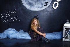 坐在演播室的小邪恶的巫婆 库存照片