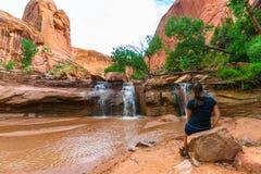 坐在瀑布前面的女孩 免版税图库摄影