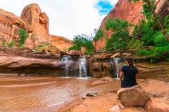 坐在瀑布前面的女孩 免版税库存照片