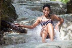 坐在瀑布的妇女 免版税库存照片