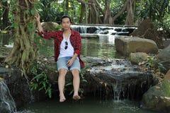 坐在瀑布附近的一个年轻轻松的人的画象 图库摄影