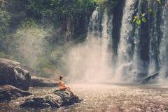 坐在瀑布附近的妇女享用太阳,在暹粒,柬埔寨的Phnom Koulen 免版税库存照片