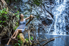 坐在瀑布附近的年轻愉快的妇女 免版税库存照片