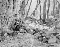 坐在火旁边在森林和读书的人(所有人被描述不更长生存,并且庄园不存在 补助 免版税库存照片